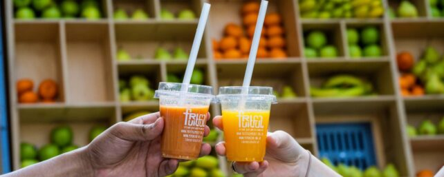 Two fruitful juices in front of Fruitful cart